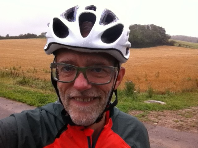 Tevreden fietser die een pain au chocola heeft gegeten